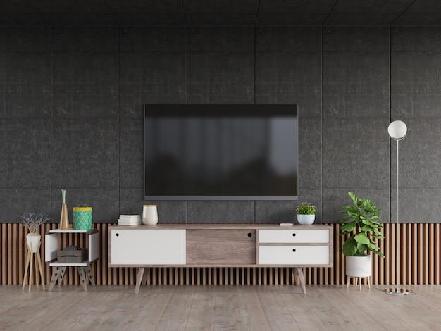 Tv en gabinete stan en la moderna sala de estar con lámpara, mesa, flores y plantas sobre fondo de pared de cemento.