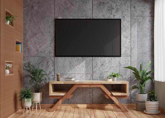 Tv en una pared de concreto oscuro en una sala de estar moderna con una pared de madera al lado y decorada con una mesa con macetas en el piso de madera. representación 3d.
