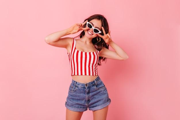 Tylish mujer de cabello oscuro en pantalones cortos de verano y top sonríe y muestra el signo de la paz en la pared rosa