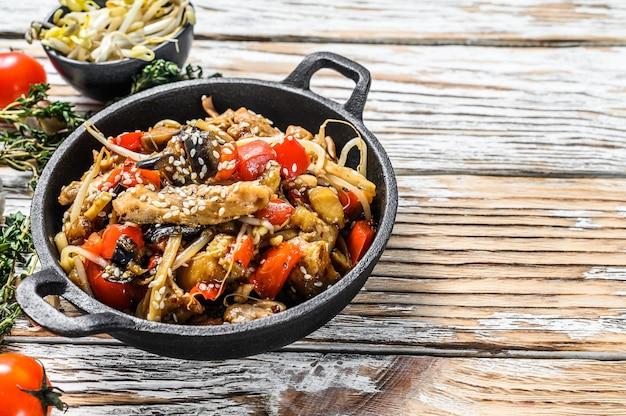 Udon fideos salteados con pollo y verduras en una sartén. fondo blanco. vista superior. copie el espacio.