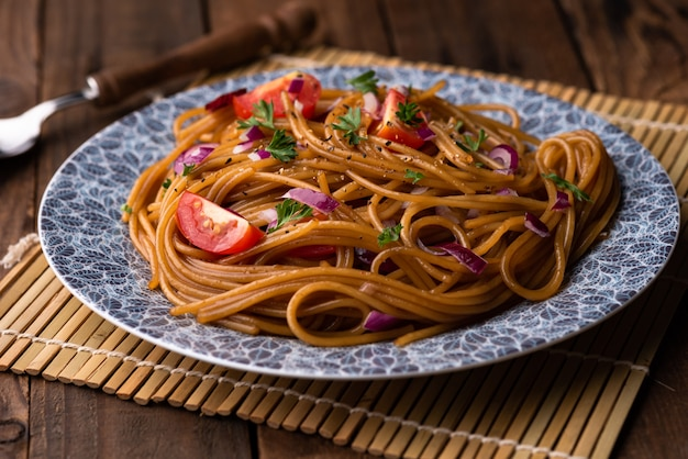 Udon saltear los fideos con verduras en un plato con palillos