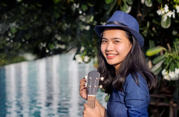 Ukelele asimiento asiático de la muchacha en la piscina