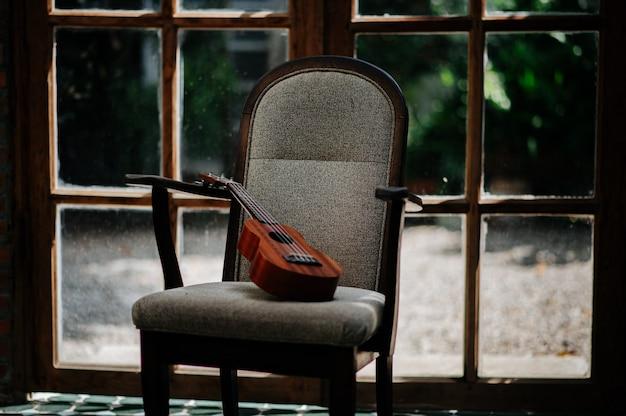 Ukelele de madera marrón descansando sobre una silla de madera