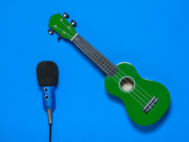 Ukelele y micrófono con cable azul sobre fondo azul.