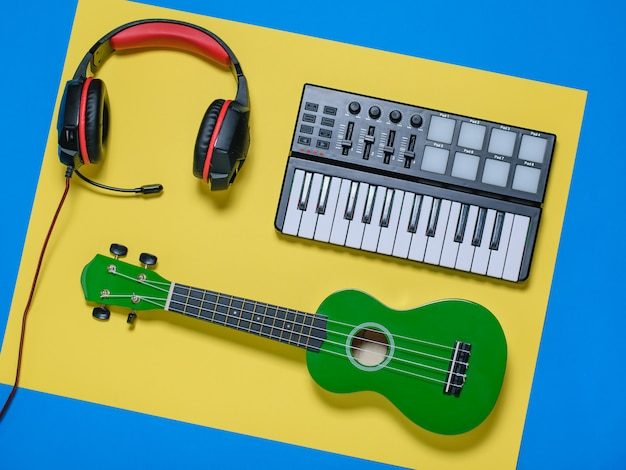 Ukelele, teclado y auriculares con cable sobre fondo azul y amarillo. la vista desde la cima.