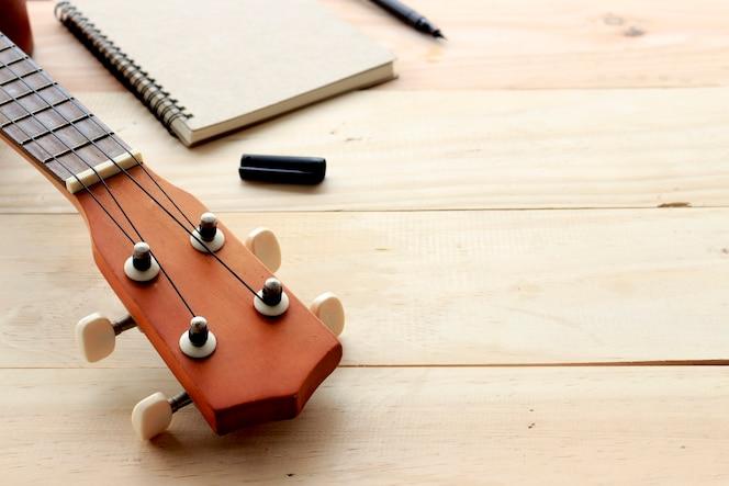Ukelele y cuaderno sobre madera