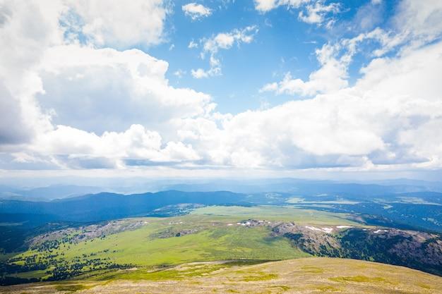Ultra amplio panorama del horizonte. montañas verdes cubiertas de bosque en el fondo de cielo azul.