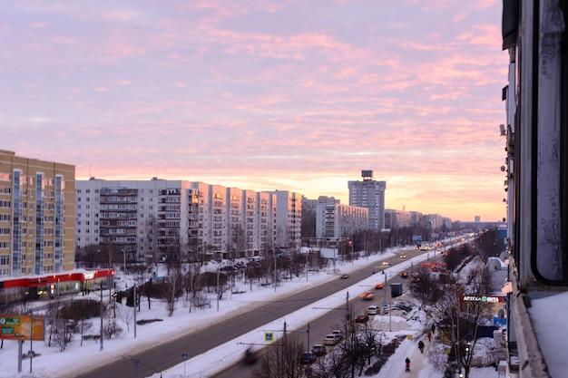 Ulyanovsk / rusia - 9 de febrero de 2019. una espaciosa calle de invierno en el distrito de new town, ulyanovsk. paisaje de la ciudad de invierno en la puesta de sol.