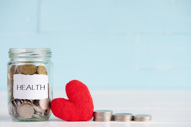 Un frasco contiene monedas con corazón rojo sobre fondo blanco de madera.