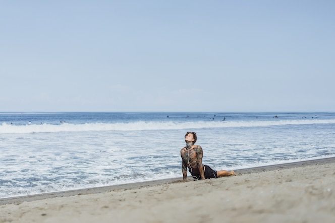 Un hombre en la costa del océano se dedica a los deportes, haciendo gimnasia