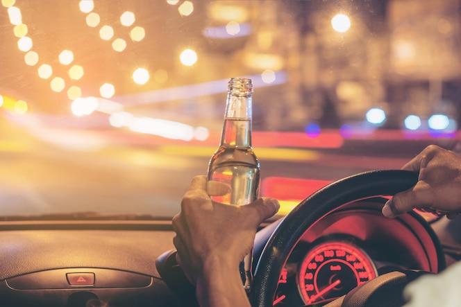 Un joven borracho conduce un automóvil con una botella de cerveza.