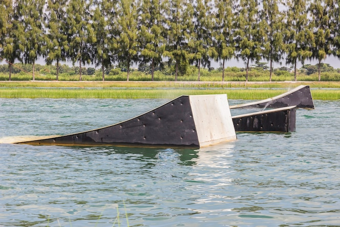Un wakeskater se desliza a través de un enorme obstáculo flotante detrás de un bote