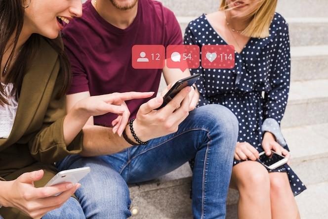 Una amiga apuntando al hombre usando iconos de notificación de red social sobre el móvil