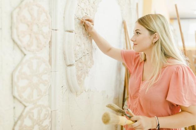 Una artista femenina talla en la pared con la herramienta