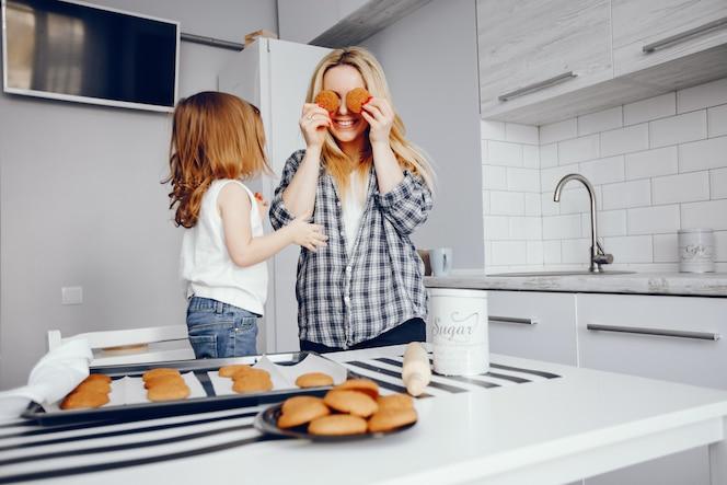 Una hermosa joven madre con su pequeña hija está cocinando en la cocina en casa