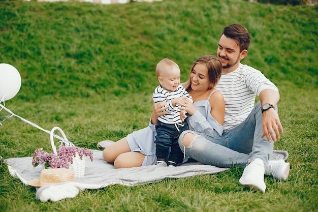 Una joven y hermosa madre rubia con un vestido azul, junto con su hombre guapo