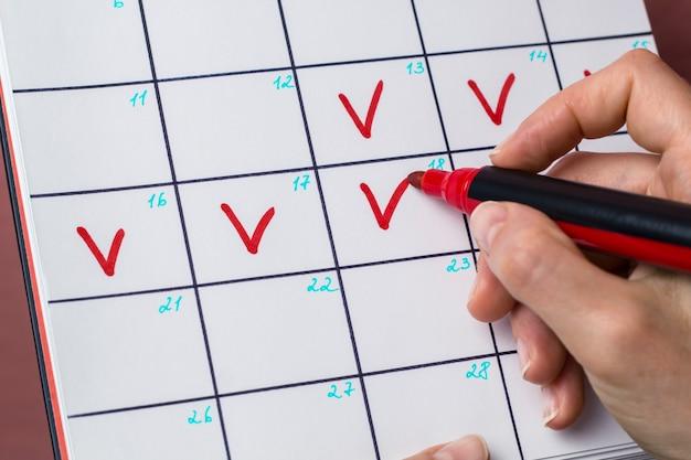 Una mujer marca los días menstruales en el calendario