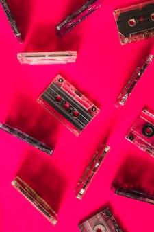 Una vista aérea de cinta de cassette transparente sobre fondo rosa