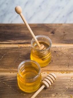 Una vista aérea de cucharón de miel con miel olla en la mesa de madera