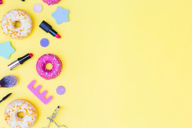 Una vista aérea de donuts; lápiz labial; rizador de pestañas; cepillo de maquillaje y separador de dedos sobre fondo amarillo