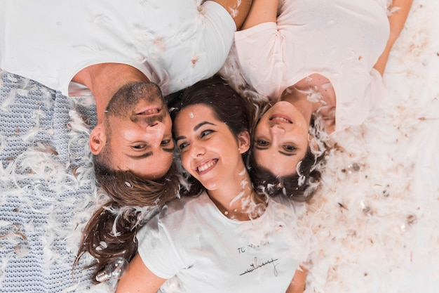 Una vista aérea de plumas blancas sobre amigos acostados en la cama