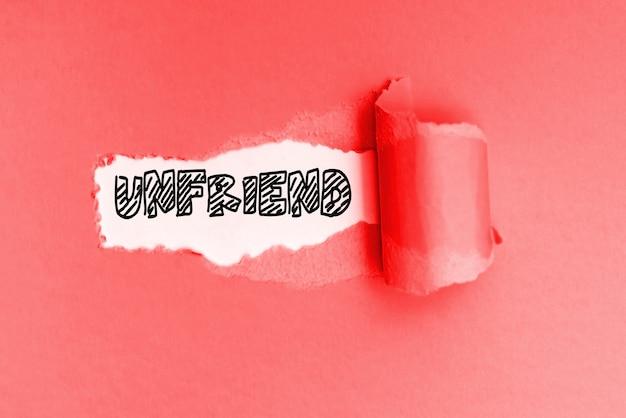 Unfriend es una palabra nueva en inglés, escrita en un papel rojo rasgado