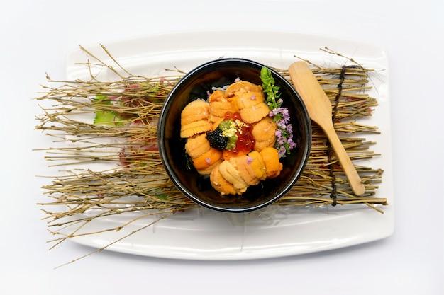 Uni don (uni en el arroz) en un tazón negro en el plato blanco y blanco bac