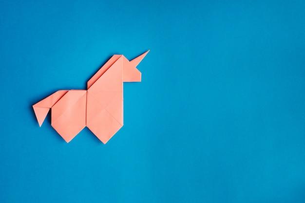 Unicornio origami rosa sobre fondo azul.