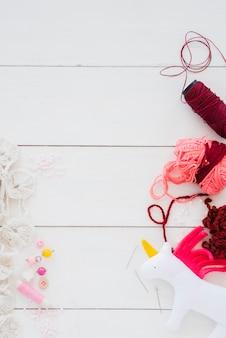 Unicornio de trapo con carrete de hilo; lana; botón; rosario; agujas en escritorio de madera