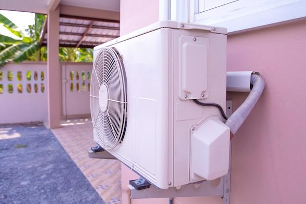 Unidad de compresor para aire acondicionado tipo pared instalada en el exterior del edificio.