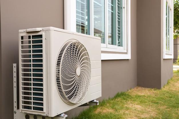 Unidad exterior del compresor del aire acondicionado instalada fuera de la casa