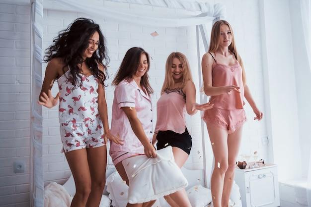 Unidad de personas en las vacaciones. confeti en el aire. las chicas jóvenes se divierten en la cama blanca en una bonita habitación
