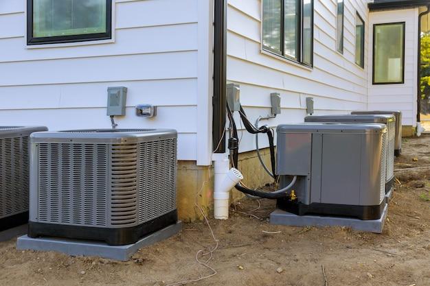 Unidad de sistema de aire acondicionado instalada fuera de la fachada de la nueva casa