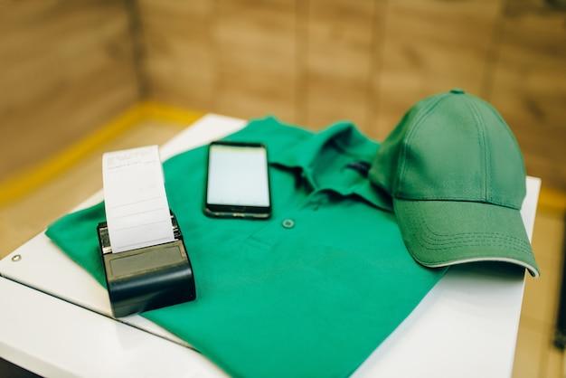 Uniforme y caja registradora sobre la mesa.