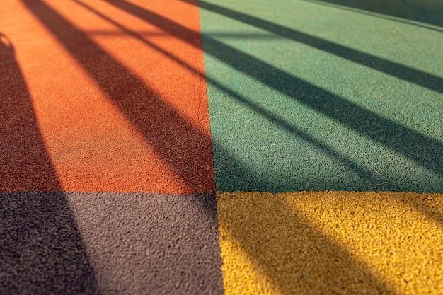 Unión de cuatro cuadrados multicolores de revestimiento de suelo con largas sombras. revestimiento de suelo acolchado con gránulos de goma. recubrimiento de goma especial para el parque infantil o actividad deportiva.