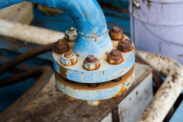 Unión industrial de tuberías azules con herrumbre y juntas