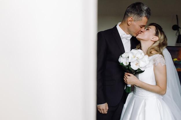 Unión novio besos novia tierna de pie en una habitación de hotel