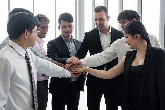 Unirse a las manos del equipo de personas asiáticas y extranjeras.
