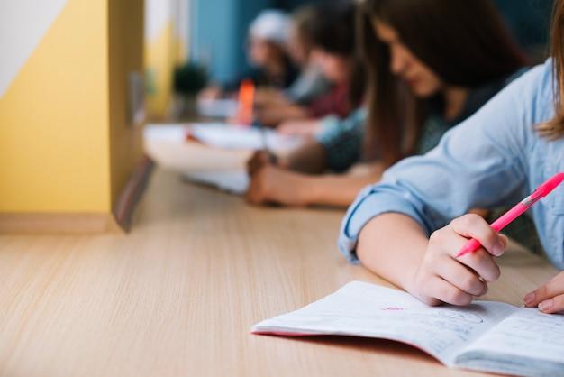 Unrecognizable colegiala escribiendo en el bloc de notas