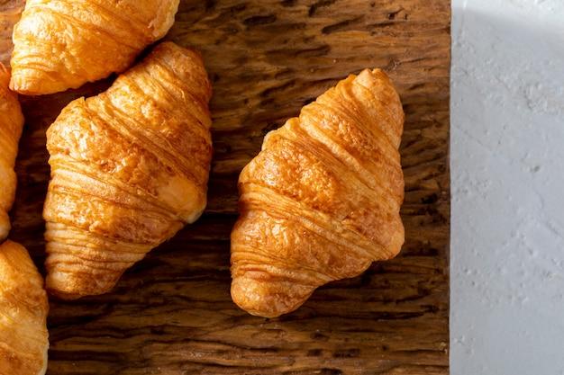 Unte con mantequilla los cruasanes en una tabla de madera rústica.