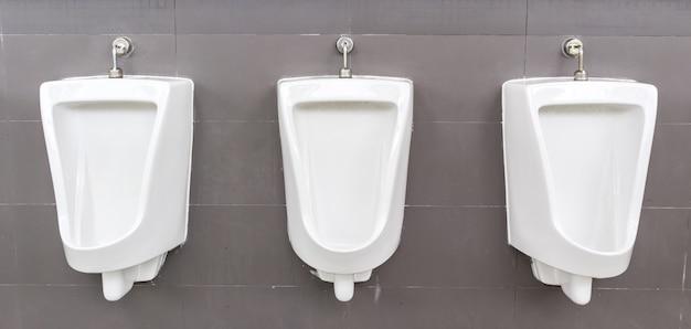 Urinarios blancos en baño de hombres