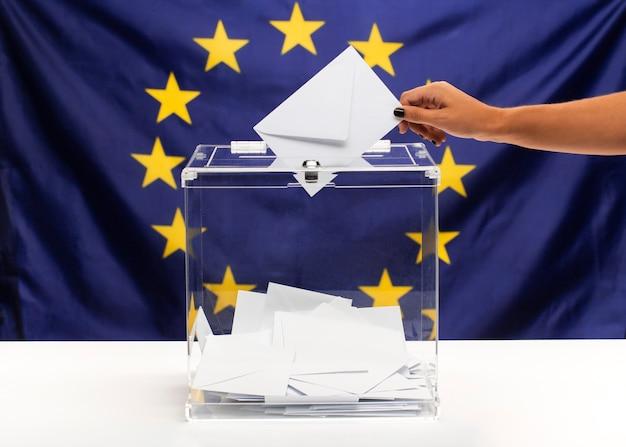 Urna transparente llena de sobre blanco y vista frontal de la bandera de la unión europea
