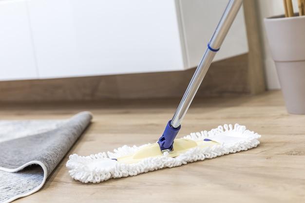 Se usa un trapeador blanco moderno para limpiar un piso de madera