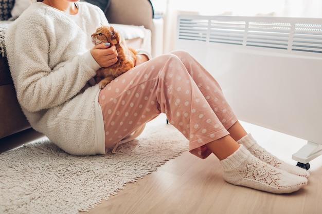 Usando el calentador en casa en invierno. mujer calienta el cuerpo con gato. temporada de calefacción.