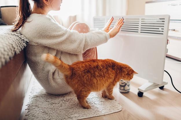 Usando calentador en casa en invierno. mujer que se calienta las manos con el gato. temporada de calefacción.