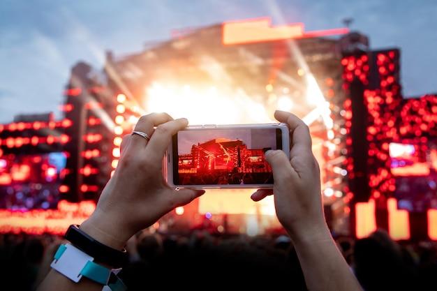 Usando la cámara del teléfono móvil para tomar fotografías y videos en un concierto en vivo al aire libre.