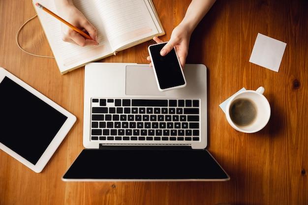 Usando dispositivos. cerca de manos femeninas caucásicas, trabajando en la oficina. concepto de negocio, finanzas, trabajo, compras en línea o ventas. copyspace para publicidad. freelance en educación, comunicación.