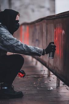 Usando lata de pintura en aerosol para hacer un cartel de protesta. hombre carismático con identidad oculta hace vandalismo.
