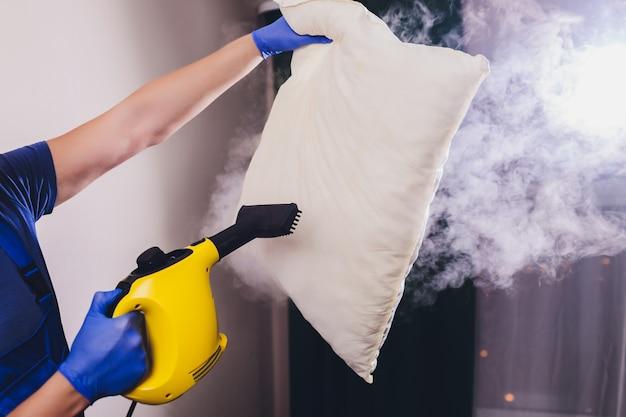 Usando un limpiador de vapor seco para desinfectar la almohada.