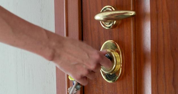 Usando una llave para abrir la cerradura de la puerta principal